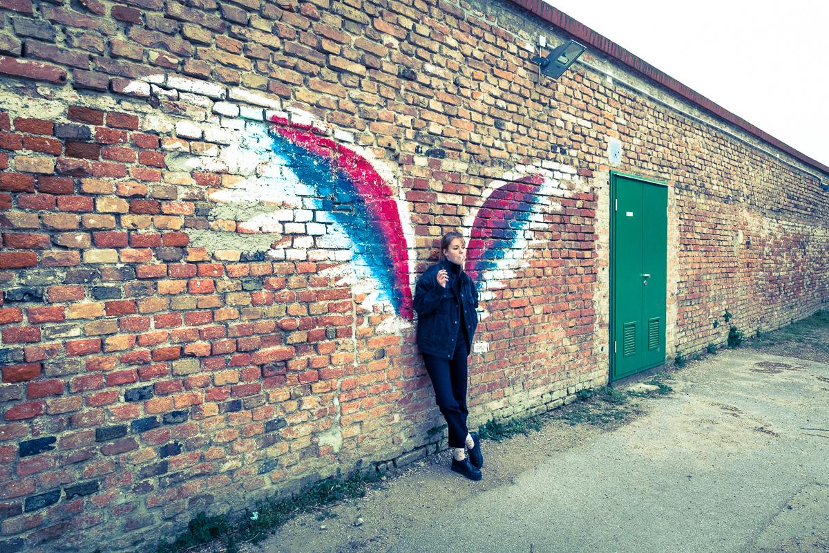 eine rauchende Frau geht an einer Mauer, auf der Engelsflügel aufgemalt sind