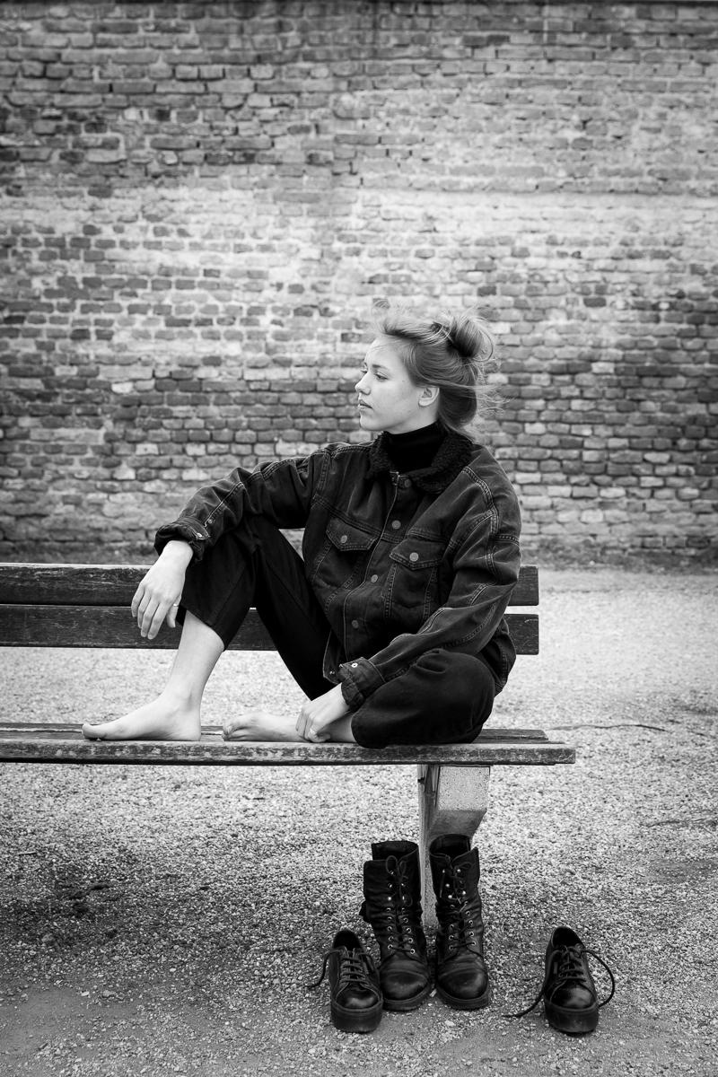 eine Frau sitzt barfuss auf einer Parkbank
