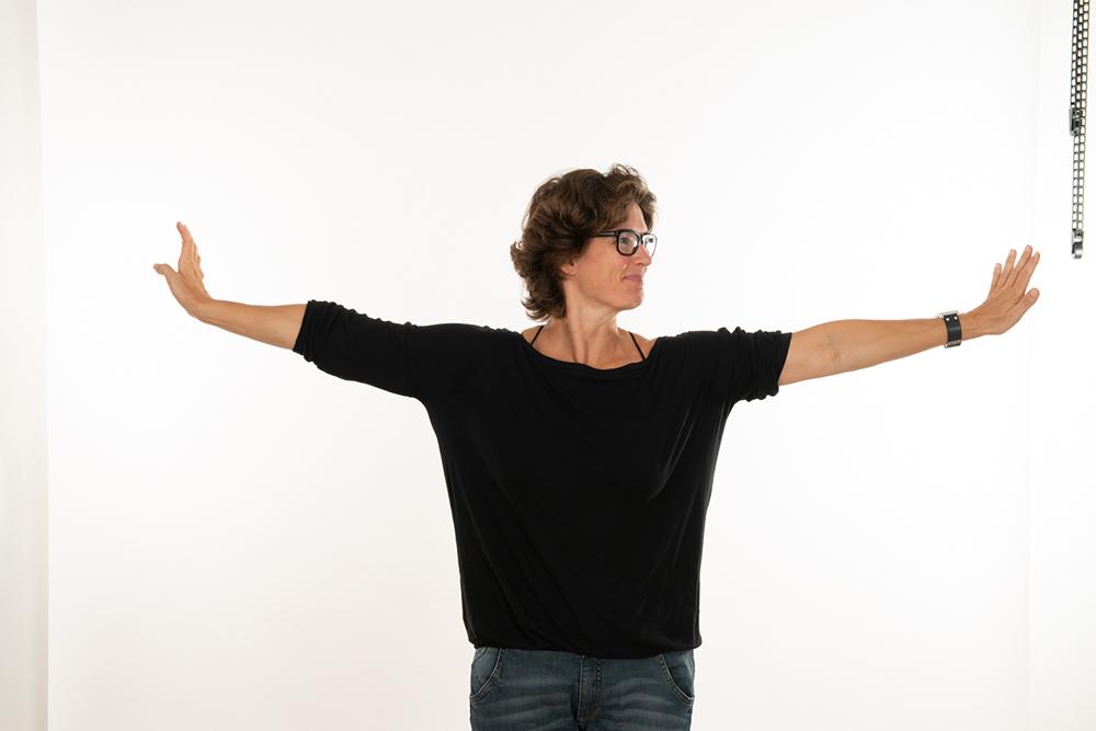 Frau mit ausgebreiteten Armen im schwarzen T-Shirt