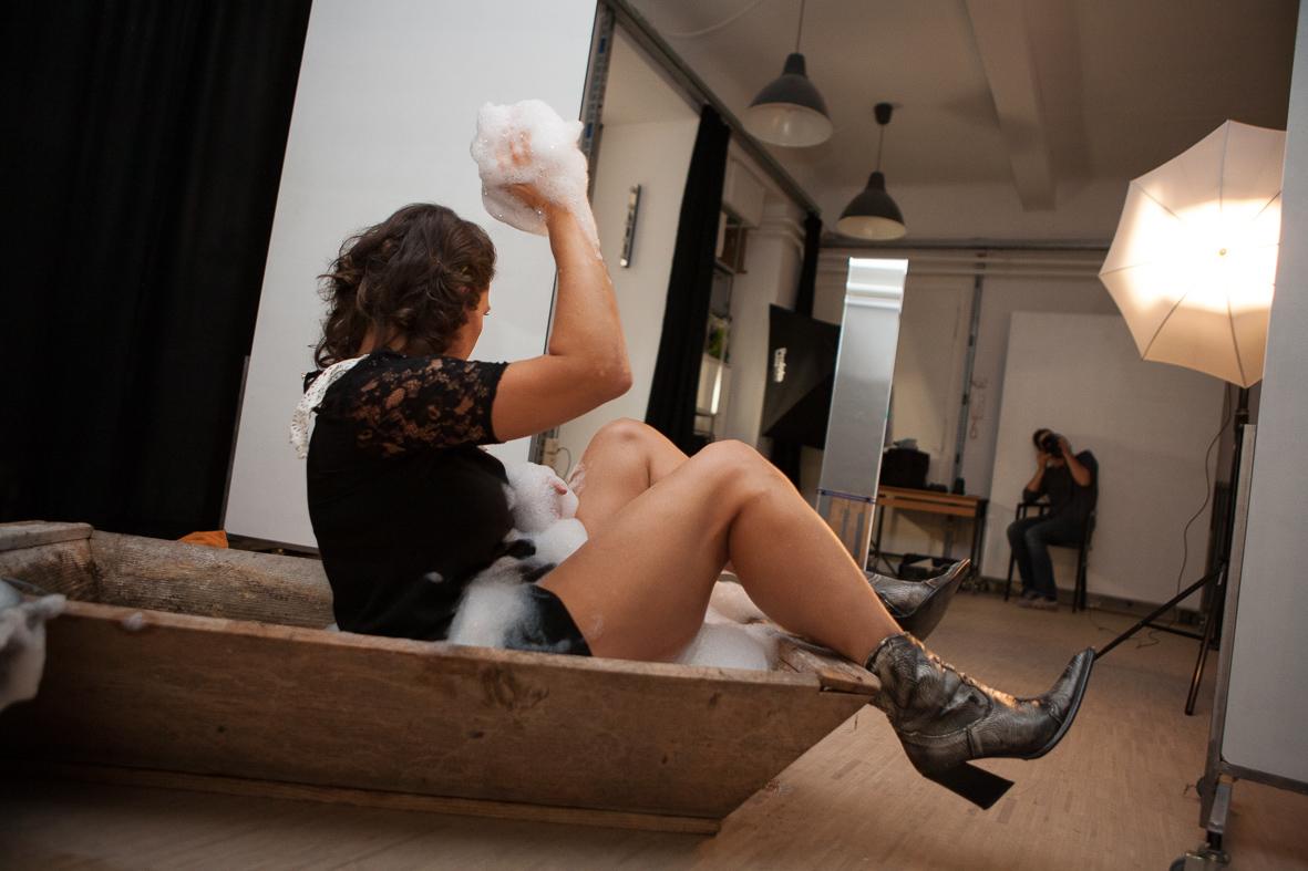 Frau mit Badeschaum in einem Holzzuber sitzend
