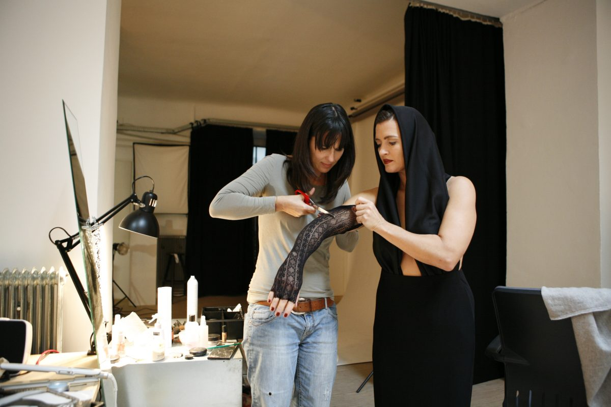 eine Frau schneidet etwas an einem langen Handschuh mit einer Schere ab