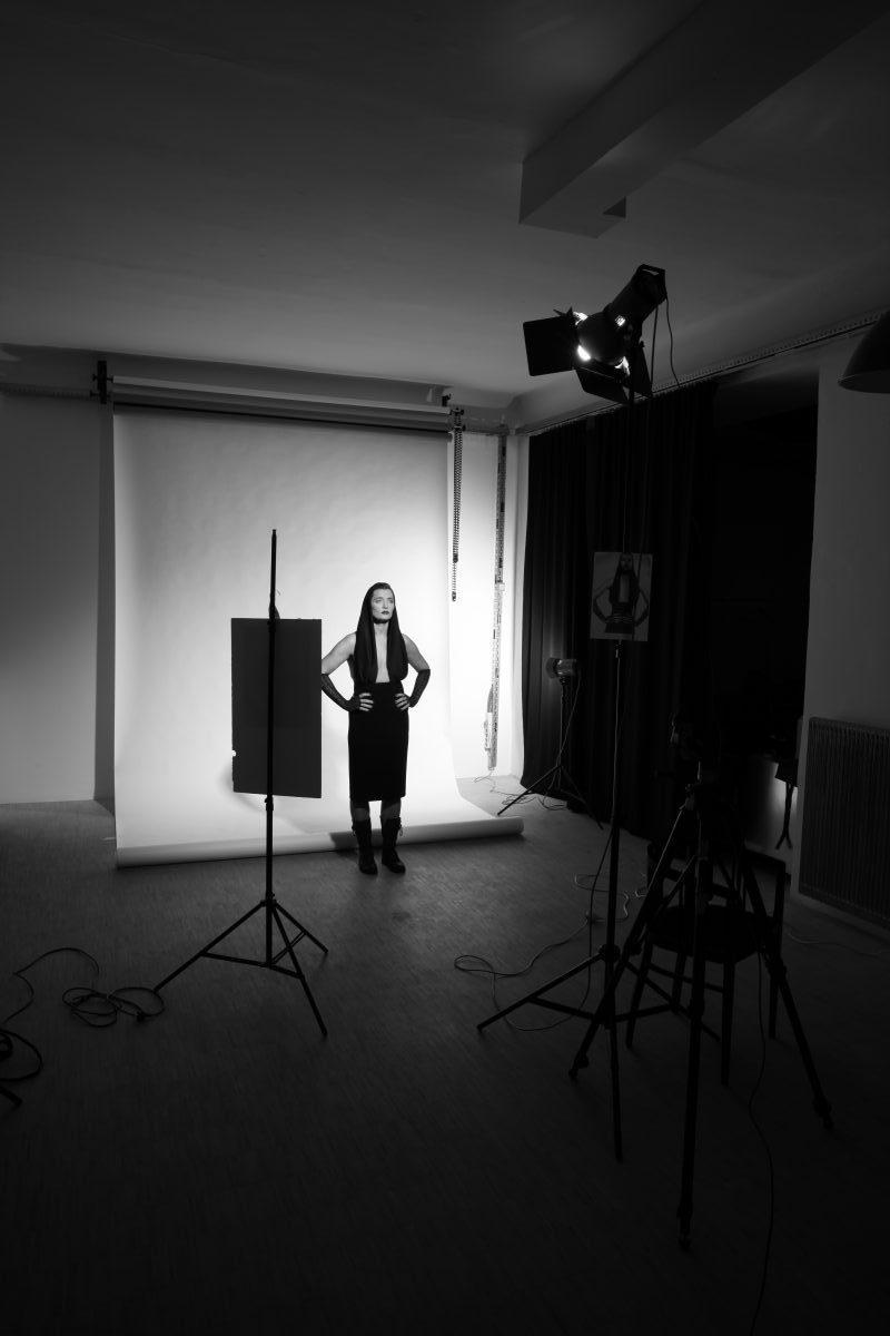 Frau vor weissem Hintergrund mit schwarzem Kleid