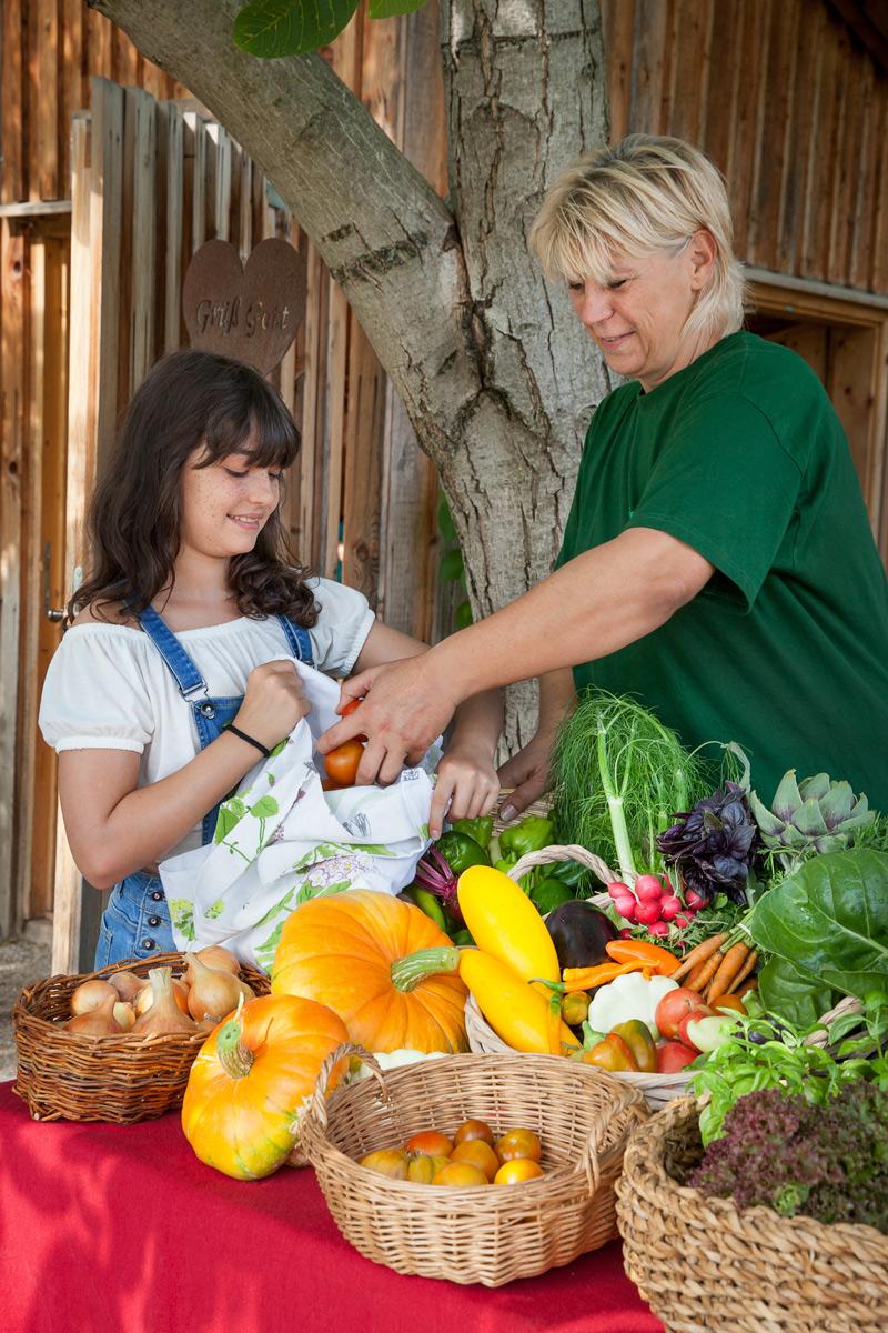 Mädchen kauft Biolebensmittel im Ökogarten Bio-Gärtnerei