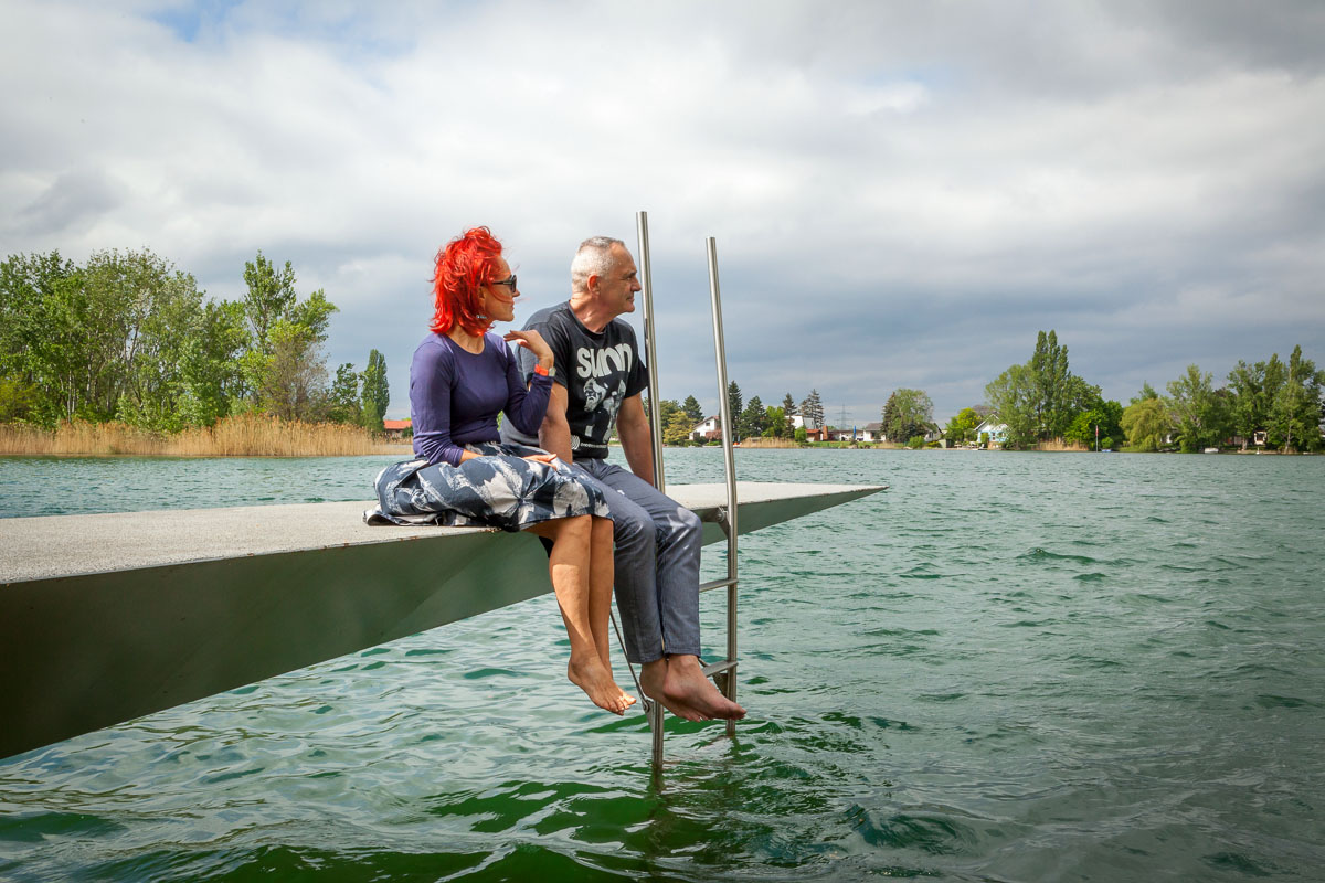 Anna Heindl und Manfred Wakolbinger sitzen an einem See auf einem Steg, designd by Eichinger und Knechtl
