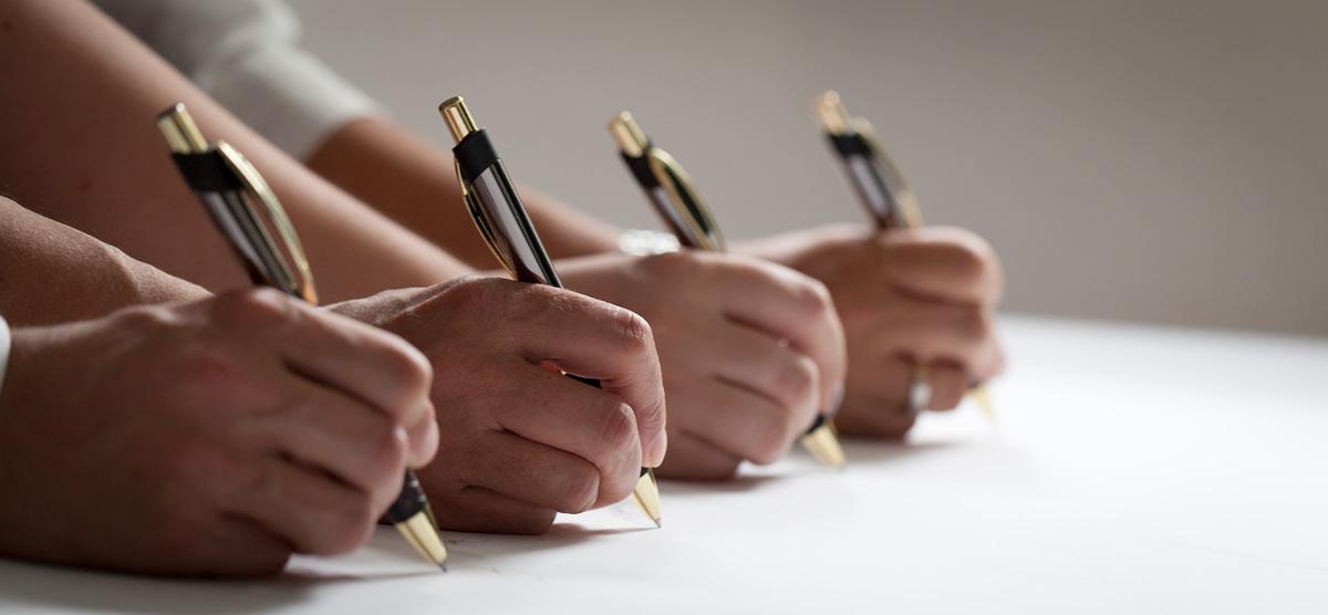 4 hände, die mit je einem kugelschreiber schreiben